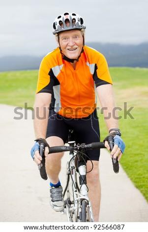happy active senior man riding bicycle outdoors - stock photo