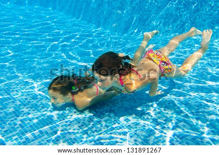 Happy active underwater children swim in pool, beautiful healthy girls swimming and having fun on family summer vacation, kids sport concept