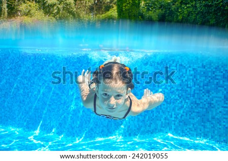 Happy active underwater girl swims in pool, beautiful healthy child swimming and having fun on family summer vacation, kids sport  - stock photo