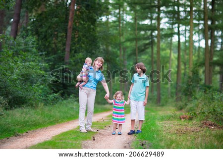 Happy active woman enjoying hiking with three children, school age boy, cute toddler girl and a little baby, walking together in a beautiful pine wood forest on a sunny summer day - stock photo