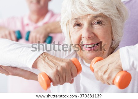 Happy active woman exercising with dumbbells - stock photo