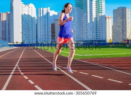 Happy active woman jogging on track, running and working out on stadium, sport and fitness in modern city