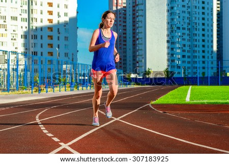 Happy active woman jogging on track, running and working out on stadium, sport and fitness in modern city, urban background  - stock photo