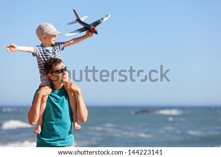 happy adorable boy holding toy plane and sitting on his young handsome father shoulders and having fun together outdoors - stock photo