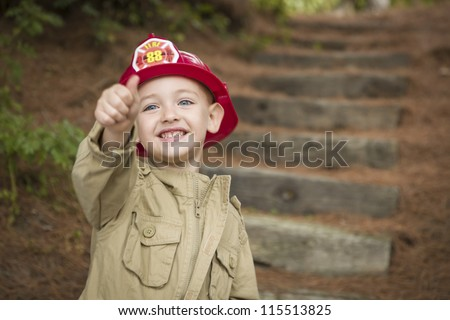Happy Adorable Child Boy with Fireman Hat and Thumbs Up Playing Outside. - stock photo