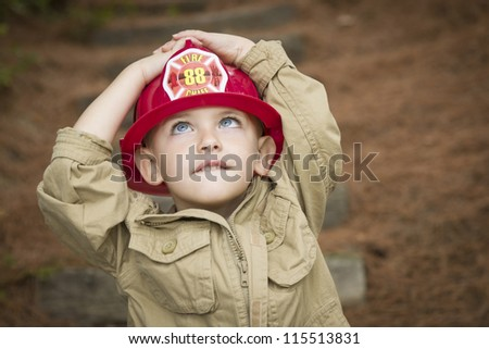 Happy Adorable Child Boy with Fireman Hat Playing Outside. - stock photo