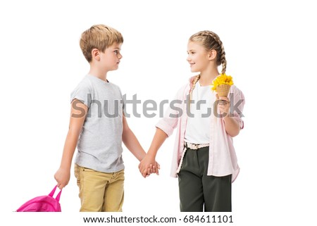 happy adorable children holding backpack and yellow flowers while standing together and holding hands isolated on white