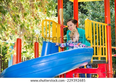 Happy adorable girl with mom on children's slide on playground near kindergarten Montessori on summer day - stock photo