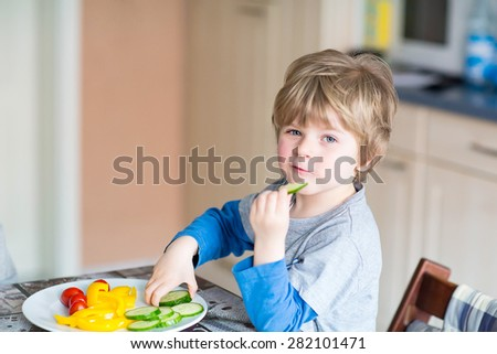 Happy adorable kid boy eating healthy food in kindergarten or at home. Fresh vegetables as snack for children. - stock photo