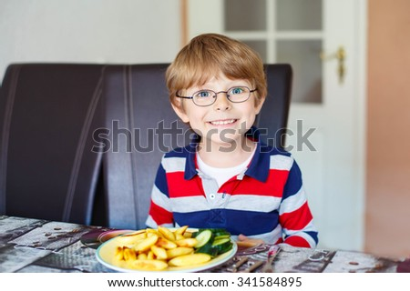 Happy adorable kid boy with glasses eating healthy food in kindergarten or at home. Fresh vegetables as snack for children. - stock photo