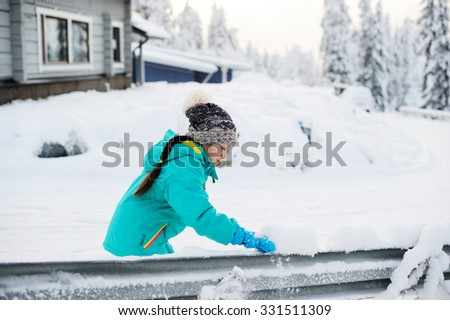 Happy adorable kid girl wearing a colorful jacket and snowpants and knitted hat playing  in a beautiful snowy winter park on beauty day - stock photo
