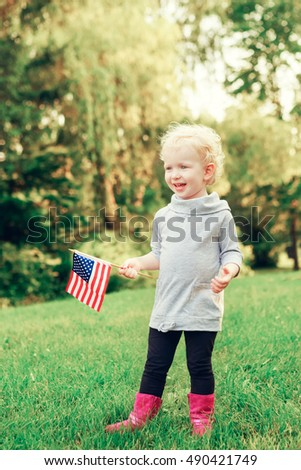 Happy adorable little blond Caucasian girl smiling laughing holding and waving American flag outside  celebrating 4th july,  Independence Day, Flag Day concept.