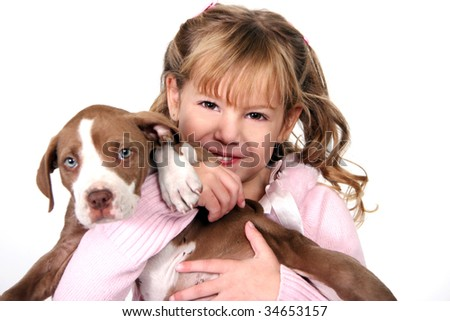 Happy Adorable Little Girl Holding Her Puppy on White Background. Girl in Focus, Puppy is Not. - stock photo