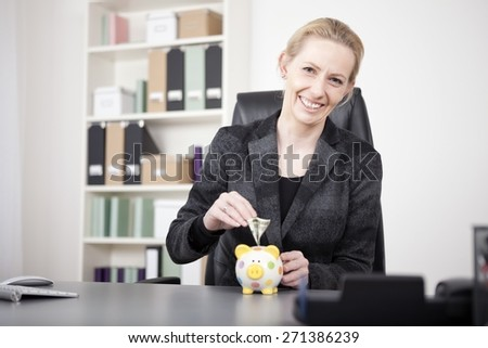 Happy Adult Businesswoman Putting Money on her Cute Piggy Bank on the Table While Looking at the Camera. - stock photo