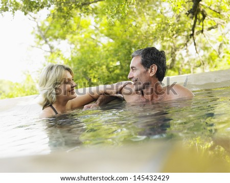 Happy adult couple in swimming pool against trees - stock photo