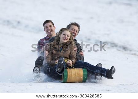 Happy adult family enjoying some winter fun on a toboggan. - stock photo