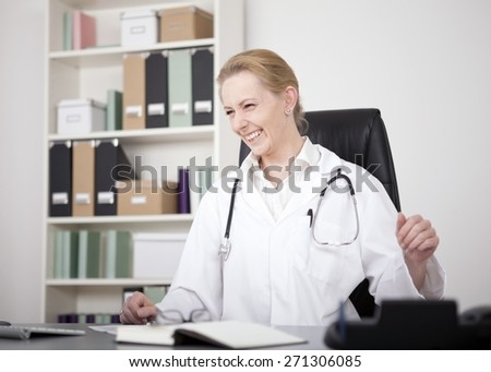 Happy Adult Female Medical Doctor, with Stethoscope on her Shoulders, Sitting at her Office While Looking to the Left. - stock photo