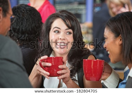 Happy adult female with coffee and friends in cafe - stock photo