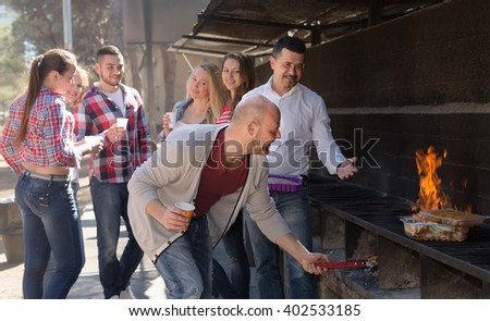 Happy adult friends making grill at summer corporate party outdoors. Selective focus - stock photo
