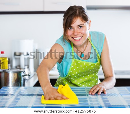 Happy adult girl dusting surfaces in kitchen interior - stock photo