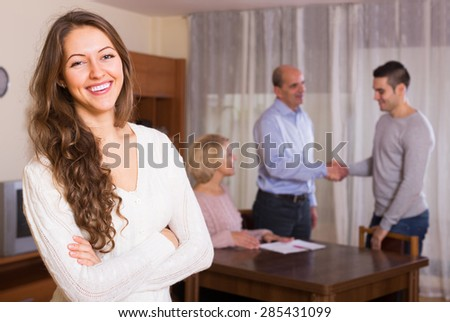 Happy adult girl staying near united family members - stock photo