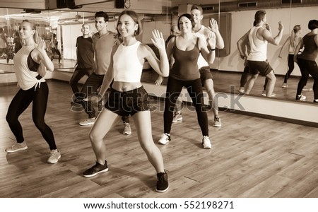 Happy adult men and ladies dancing zumba at lesson
