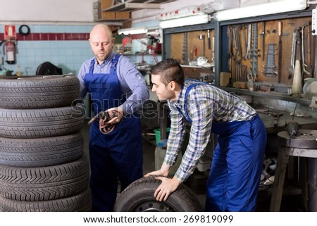 Happy adult mounting specialists working at auto repair shop. Focus on the right man - stock photo
