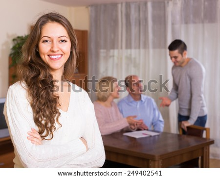 Happy adult smiling girl staying near united family members - stock photo