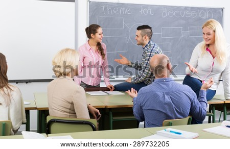 happy adult students chatting at training session for employees during break in classroom