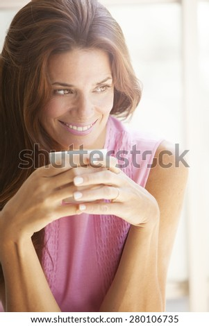 Happy adult woman drinking tea outdoors - stock photo