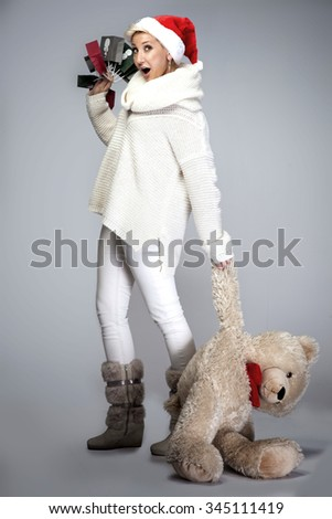 Happy adult woman in santa claus hat holding teddy bear and christmas gifts. - stock photo