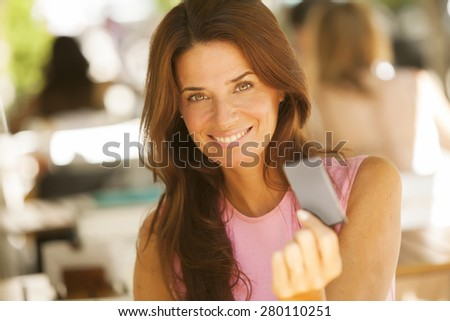 Happy adult woman paying with credit card - stock photo