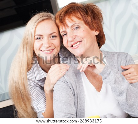Happy adult woman with daughter on kitchen. Family at home. - stock photo