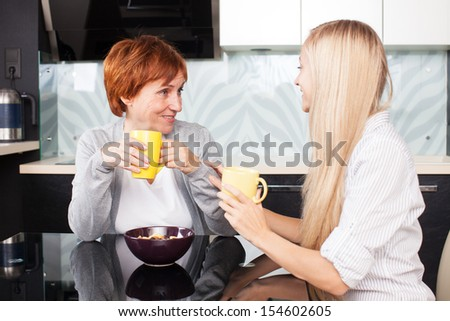 Happy adult woman with daughter on kitchen. Family at home talking and drinking tea - stock photo