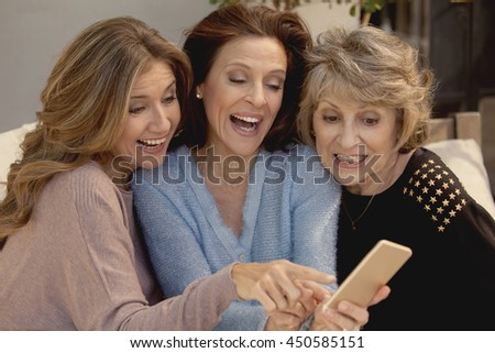Happy adult women having fun with mobile phone
