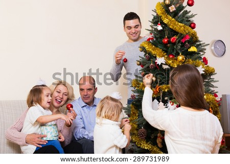 Happy adults and little kids helping grand parent decorate Xmas tree at home - stock photo