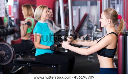 Happy adults of different age having strength training in sport club