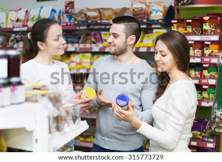 Happy adults people choosing tinned food at supermarket - stock photo