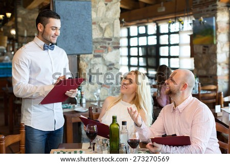 Happy adults people having dinner and respectful waiter - stock photo