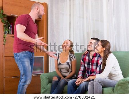 Happy adults playing charades in hall and laughing - stock photo