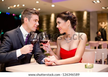 happy affectionate couple at restaurant toasting and looking at each other - stock photo