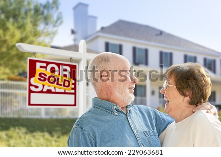 Happy Affectionate Senior Couple Hugging in Front of Sold Real Estate Sign and House.