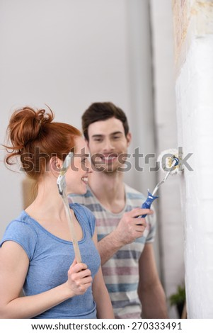 Happy affectionate young couple renovating their home standing smiling at each other as they paint a white wall - stock photo