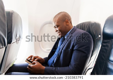 happy african airplane passenger using smart phone on plane - stock photo