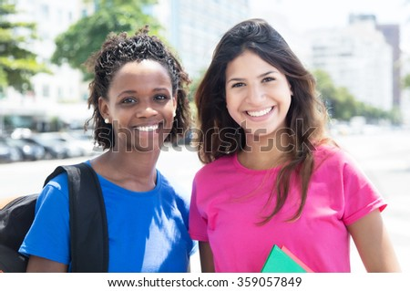 Happy african american and caucasian student in city - stock photo