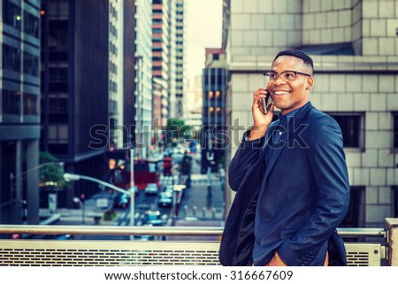 Happy African American Businessman working in New York. Wearing blue jacket, glasses, a young black man standing by railing on balcony, facing street with high buildings, smiling, talking on phone. - stock photo