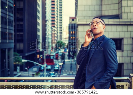 Happy African American Businessman working in New York, wearing blue jacket, glasses, standing by railing on balcony, facing street with high buildings, looking up, thinking, talking on cell phone.  - stock photo