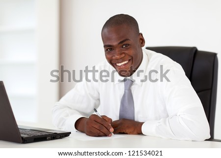happy african american businessman writing report
