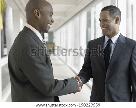 Happy African American businessmen shaking hands while standing in office corridor - stock photo