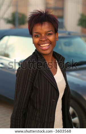 Happy African American businesswoman with new car purchase - stock photo